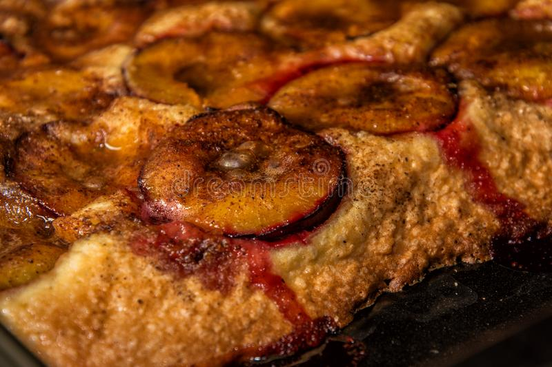 A piece of fragrant homemade plum cake on a black baking tray, sticking out from the oven royalty free stock photography