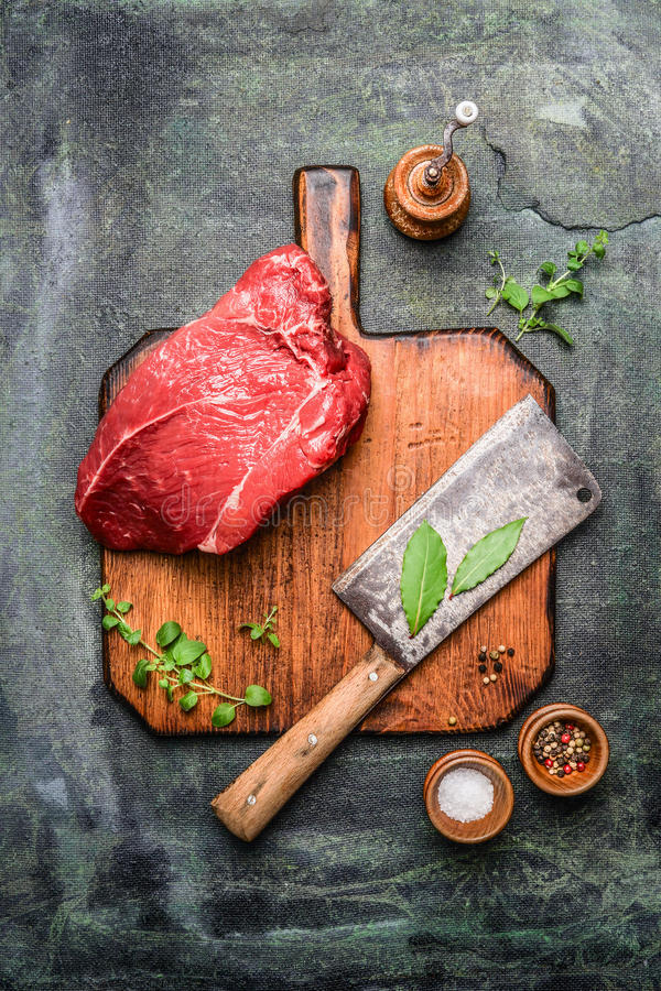 Piece of fresh beef meat on chopping board with meat cleaver large and seasoning on rustic background. Top view stock images