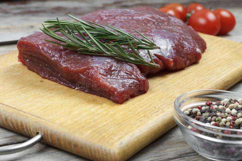 A piece of fresh beef meat on a cutting board, rosemary, pepper peas, cherry tomatoes. Closeup. Concept: cooking stock photo