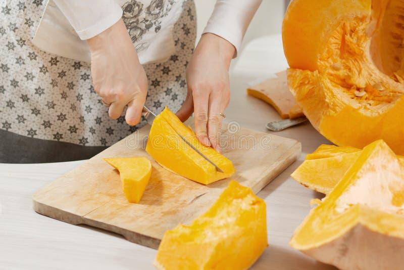 Piece of fresh pumpkin lies on a wooden kitchen board. Female hands cut pumpkins into long strips with a kitchen knife. A piece of fresh pumpkin lies on a stock photography