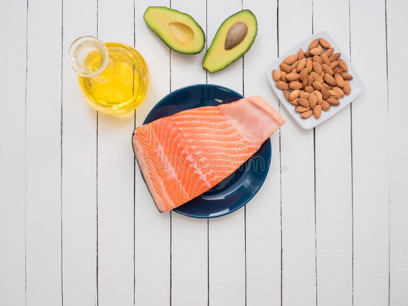 Piece of fresh salmon on a plate, avocado, almonds and sunflower oil on a table royalty free stock photos