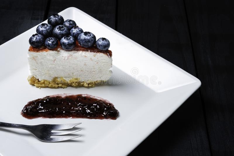 Piece of freshness delicious blueberry cheese cake in white plate is sweet baked bakery dessert on wooden table.  royalty free stock image