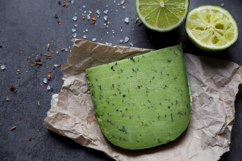 Piece of green cheese on crushed paper with lime royalty free stock photo