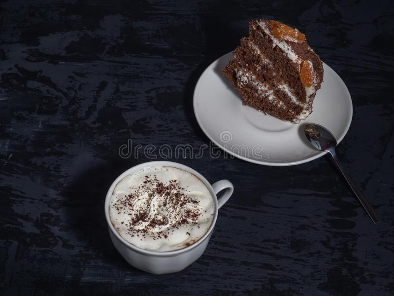 A piece of homemade cake on a white saucer and coffee with cream on a dark background royalty free stock photos