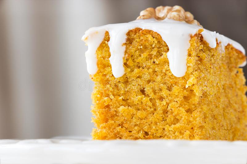 Piece of homemade carrot cake with nut and icing cream. Selective focus. Close up royalty free stock image