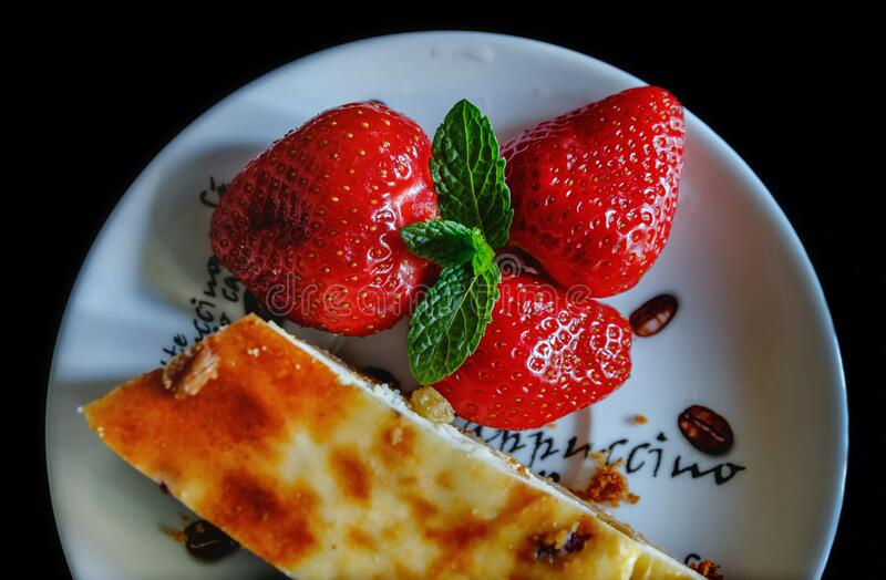 Piece of homemade cheesecake on a plate decorated with fresh strawberries and mint leaves stock images