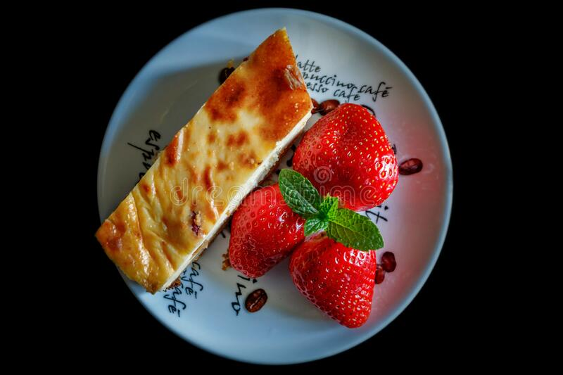 Piece of homemade cheesecake on a plate decorated with fresh strawberries and mint leaves stock photography
