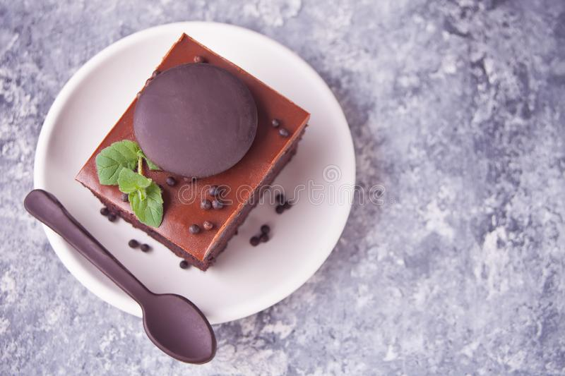 A piece of homemade chocolate cake on the plate with icing, mint leaf and chocolate spoon on the gray table stock photo