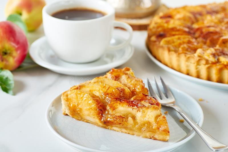 Piece of homemade french apple tart on dish and coffee stock photography