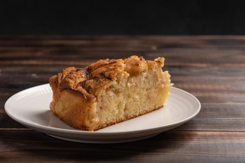 Piece of homemade traditional cornish apple pie on a white plate. Close up. Selective focus royalty free stock image