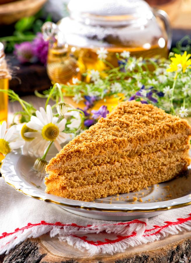Piece of honey cake close-up on white plate, linen cloth and wooden slice decorated with wild flowers stock photo