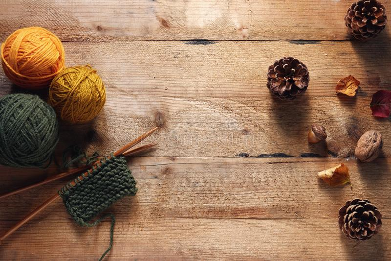 A piece of knitting with wooden needles and yarn among leaves an royalty free stock photos