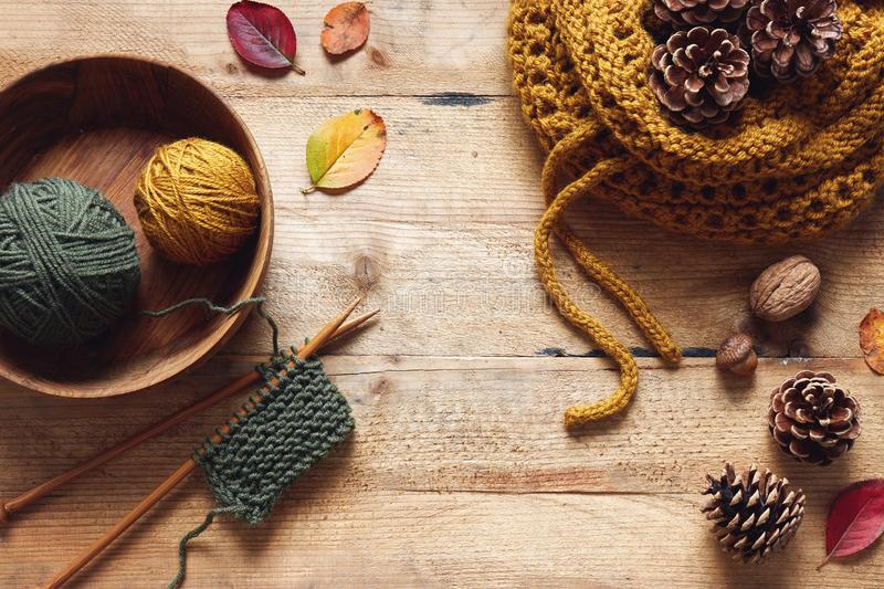 A piece of knitting with wooden needles and yarn among leaves an stock photography