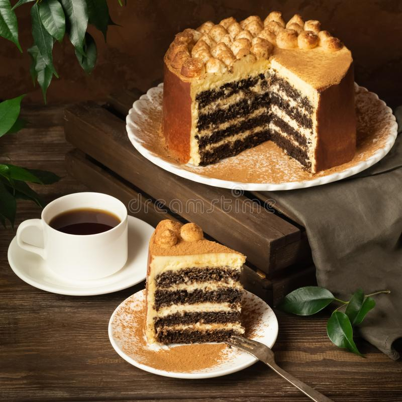 A piece from a large cake and a cup of tea or coffee on a dark background. Square frame royalty free stock images