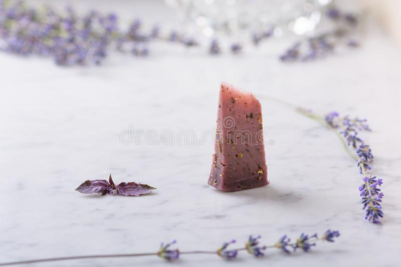 Piece of lavender cheese, lavender flowers and basil leaves on white marble table royalty free stock photos