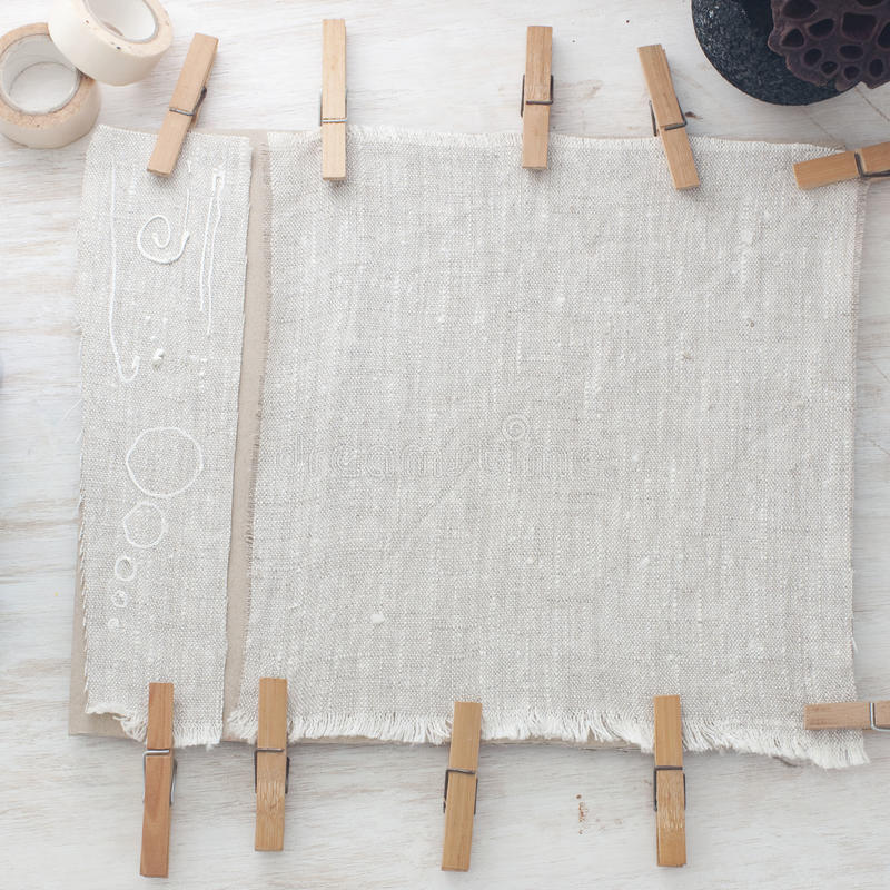Piece of linen cloth hold with wooden pins on a table. Background stock photography