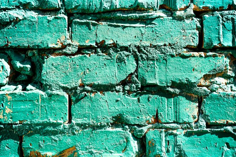 A piece of old painted in turquoise brick wall paint, a brick texture. Abstract background royalty free stock photo
