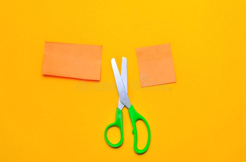 A piece of paper and scissors on a orange background, place for text, paper cutting stock photo
