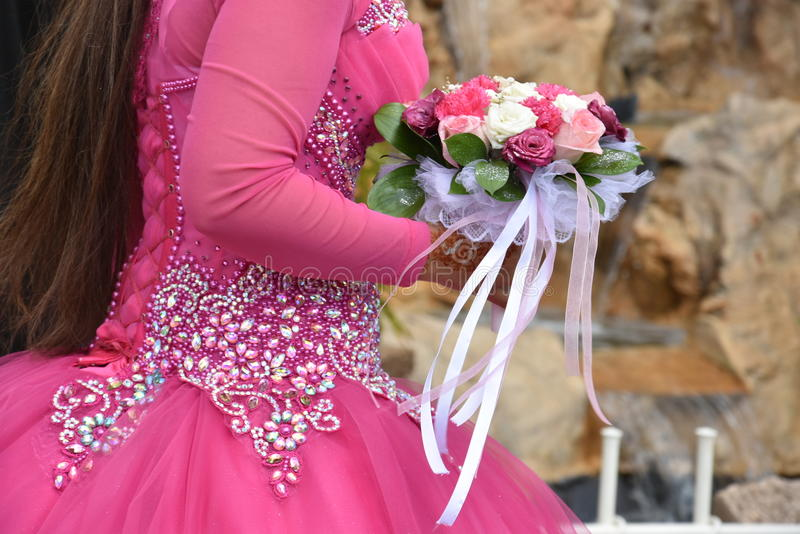A piece of pink bridesmaid dress with a bouquet. Middle East- Beersheba, Israel. April 13, Wedding dress - in Negev, Israel, the hall `Agamim`, 2016 stock photos