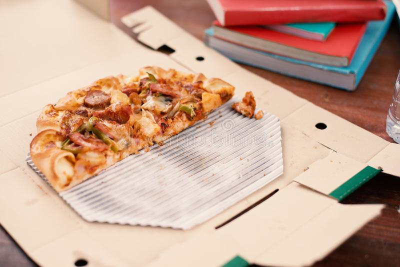 Piece of Pizza on table. Pizza on table with books and drinks for students who celebrating party after examination. Cut off pizza. In delivery box. Food and stock photos