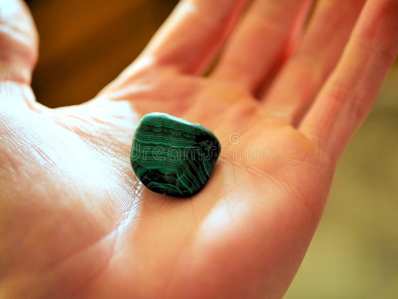 Piece of polished malachite in palm of hand. stock images