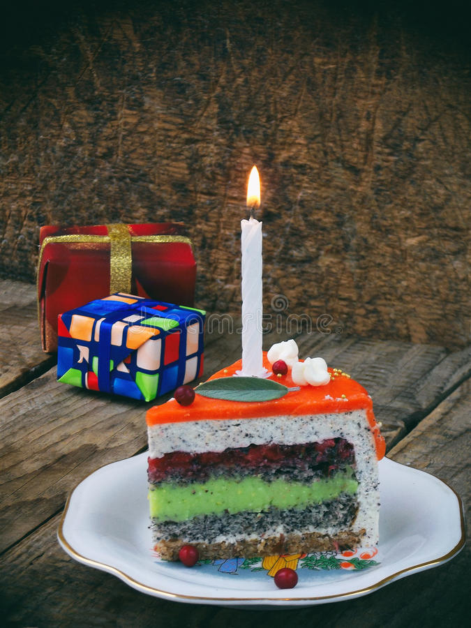 Piece of poppy cake with lime cream and strawberry jelly with a lighted candle. Happy Birthday. selective focus. stock image