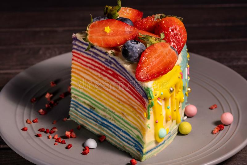 A piece of rainbow cake with strawberries and blueberries stock images