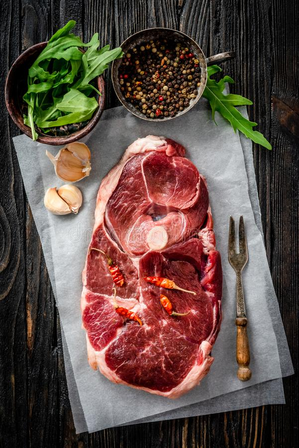 Piece of raw lamb meat. With spices on dark wooden table, top view royalty free stock image