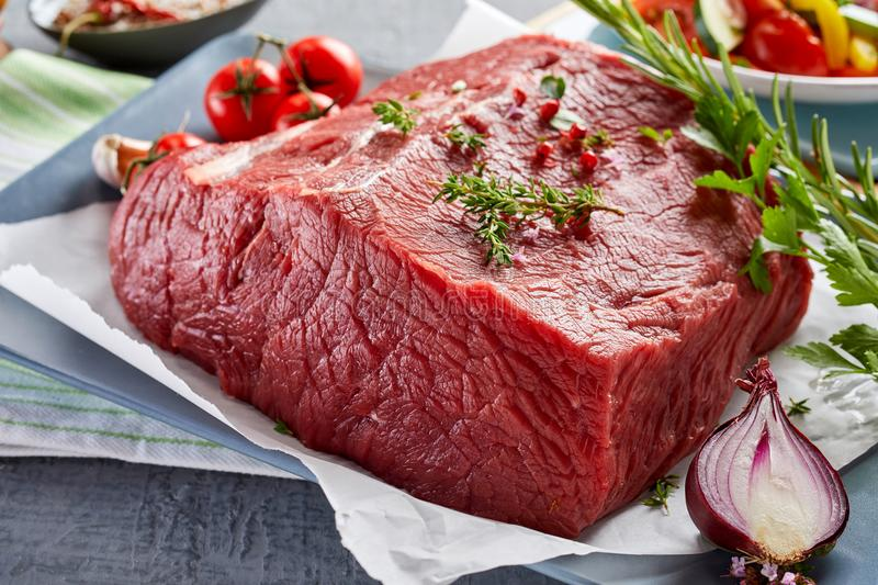Close up view of rump steak on table. Piece of raw rump steak prepared with spices on plate royalty free stock photo