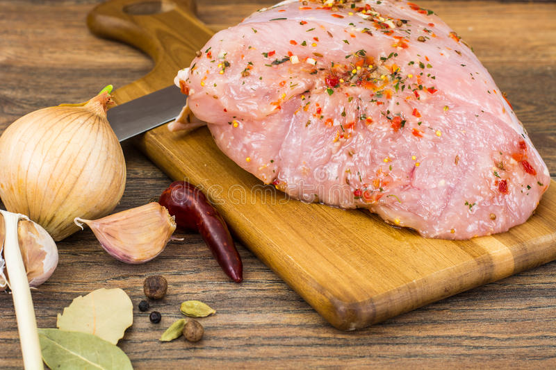 Piece of raw turkey fillet in spices royalty free stock images