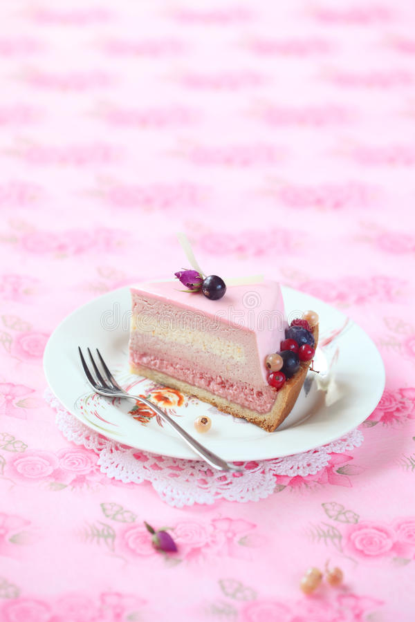 Piece of Red Currant, Rose and Lychee Mousse Cake. On a white plate and light pink floral background stock photos