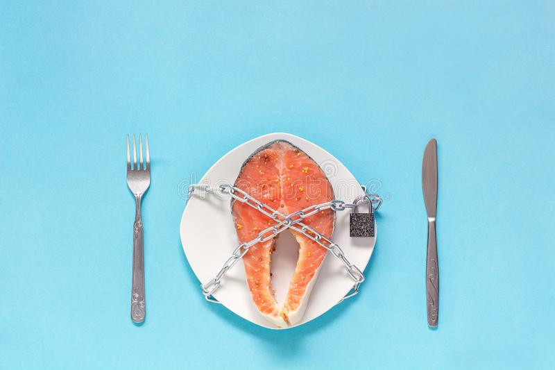 Piece of red fish on plate and chain with closed padlock royalty free stock photography