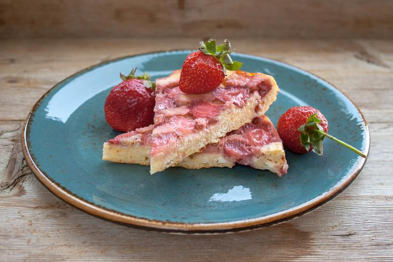 Piece of round strawberry berries tart pie pudding on blue plate on rustic wooden background stock photography