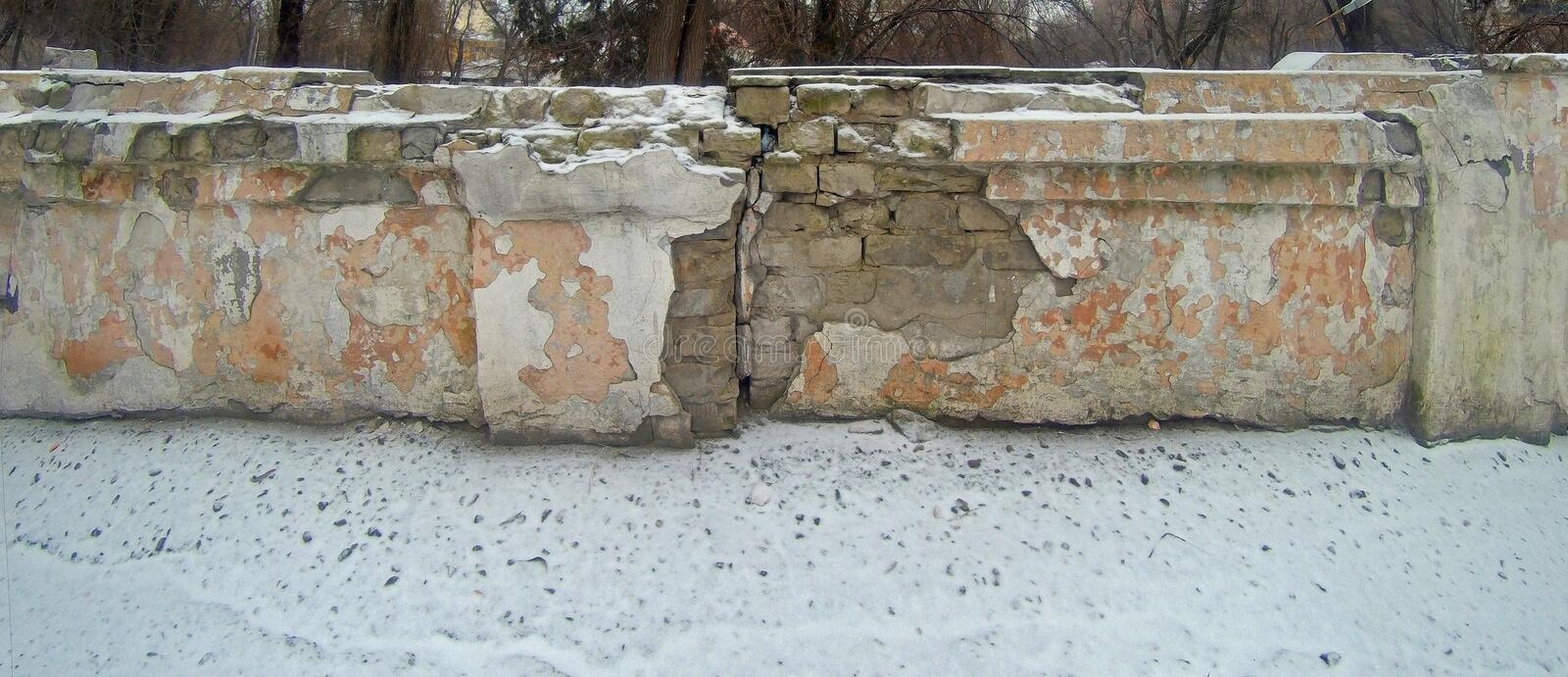 A piece of a ruined brick wall covered with snow stock images