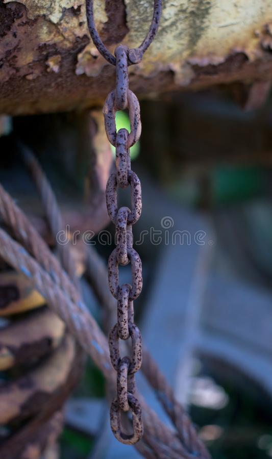 A piece of rusty chain hanging from an agricultural machine. Affordable cover book, ilustration card royalty free stock photography