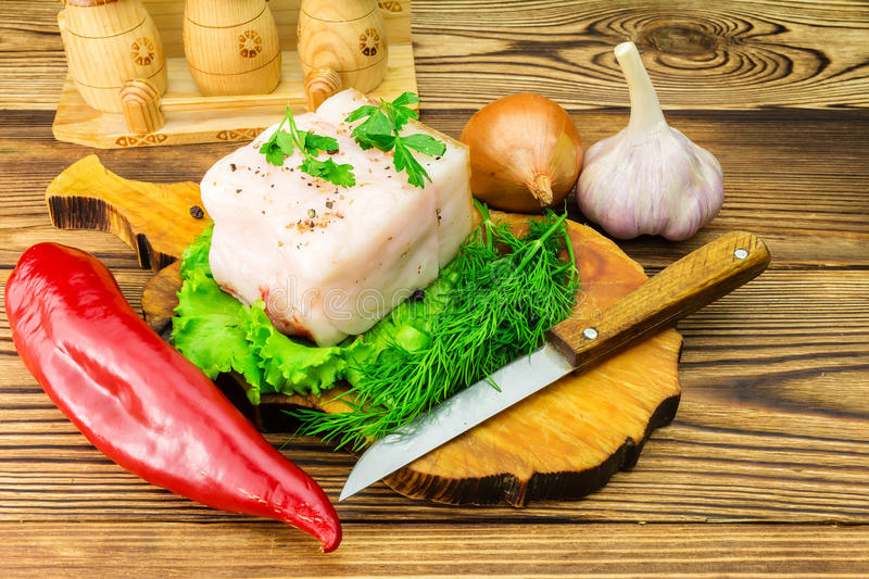 Piece and sliced fresh pork lard, fresh produce, greens, vegetables on the wooden board and knife on table. royalty free stock photo