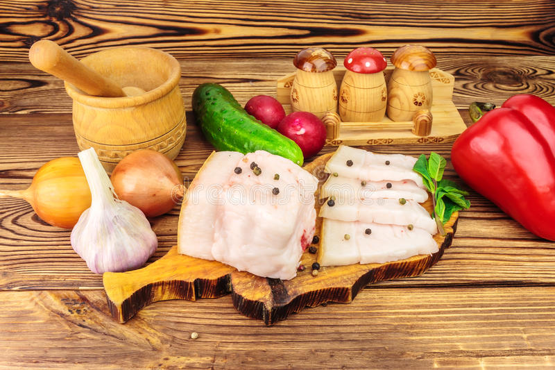 Piece and sliced fresh, raw pork lard on wooden board with vegetables, spices on the table. stock image
