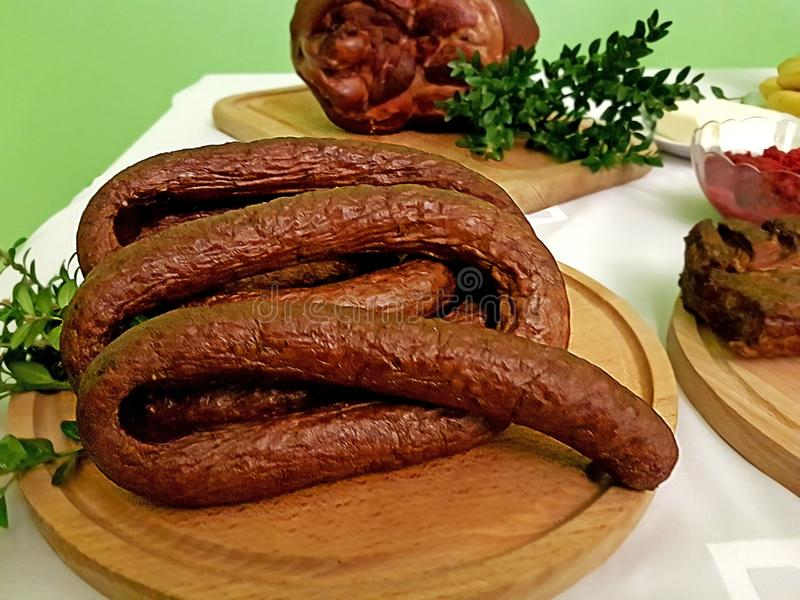 A piece of smoked sausage chopped on a wooden board decorated with a green plant. Fat high-protein high-calorie food. Taste for re royalty free stock images