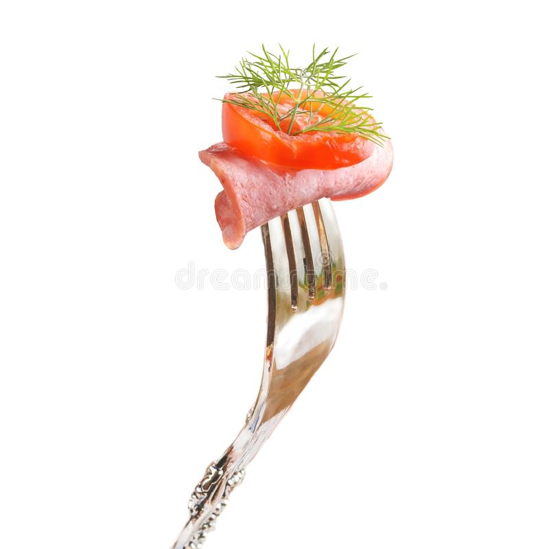 A piece of smoked sausage with tomato and dill pinned on a fork. stock photo