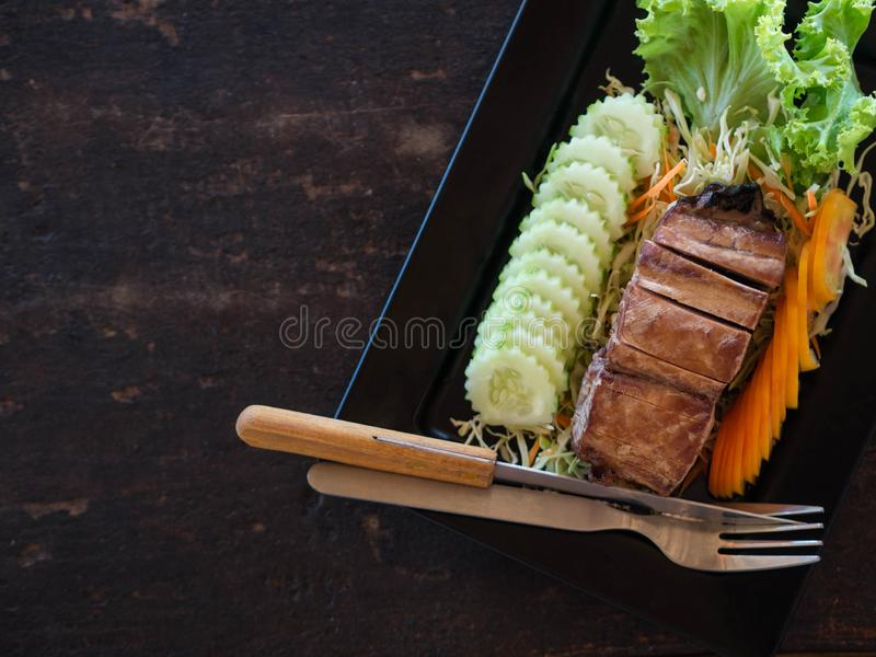 A piece of smoked sea fish with slices of fresh vegetables and cutlery on a black rectangular plate on a wooden table in a Thai. Restaurant royalty free stock image