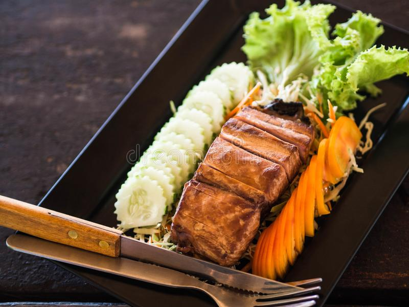 A piece of smoked sea fish with slices of fresh vegetables and cutlery on a black rectangular plate on a wooden table in a Thai. Restaurant royalty free stock images