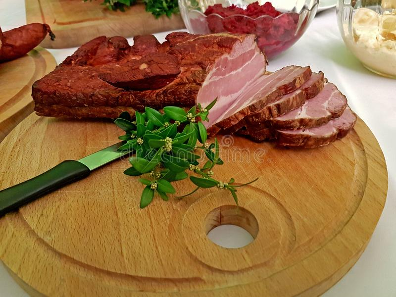 A piece of smoked sponge chopped on a wooden board decorated with a green plant. Fat high-protein high-calorie food. Taste for rea stock photos