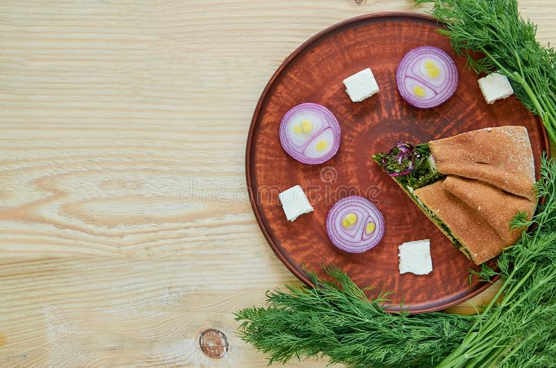 A piece of spinach pie with feta cheese, onion on the wooden table with free copy space. Decorated with fresh dill, onion rings royalty free stock photo