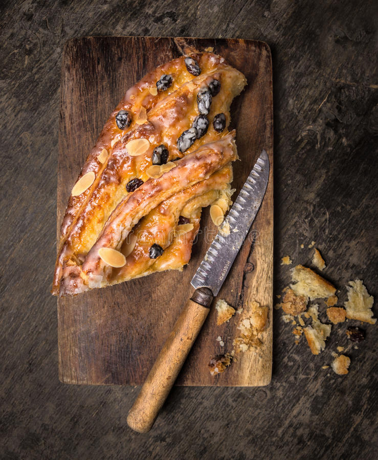 Piece of Sweet Braided Bread with raisins and roasted almonds on cutting board with knife. Piece of Sweet Braided Bread with raisins and roasted almonds on a royalty free stock image