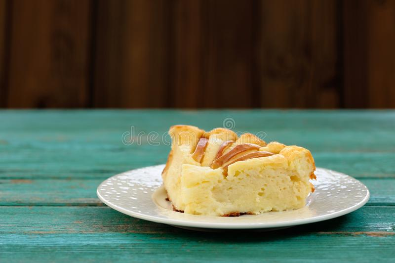 Piece of syrnik, light quark pie with apples on old wooden table royalty free stock images