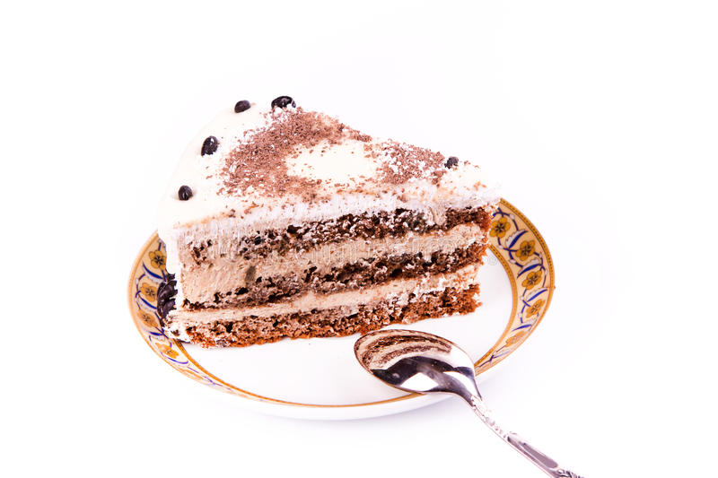A piece of tasty coffee chocolate cake on a plate with a spoon stock photos