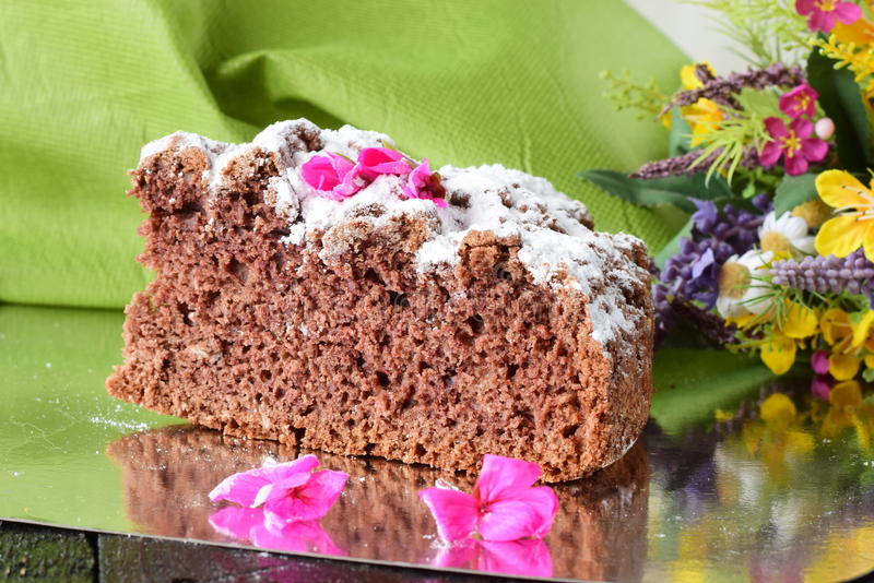 A piece of a tasty homemade chocolate cake on a silver plate with flowers and green cloth as a background. Home cooking stock photos