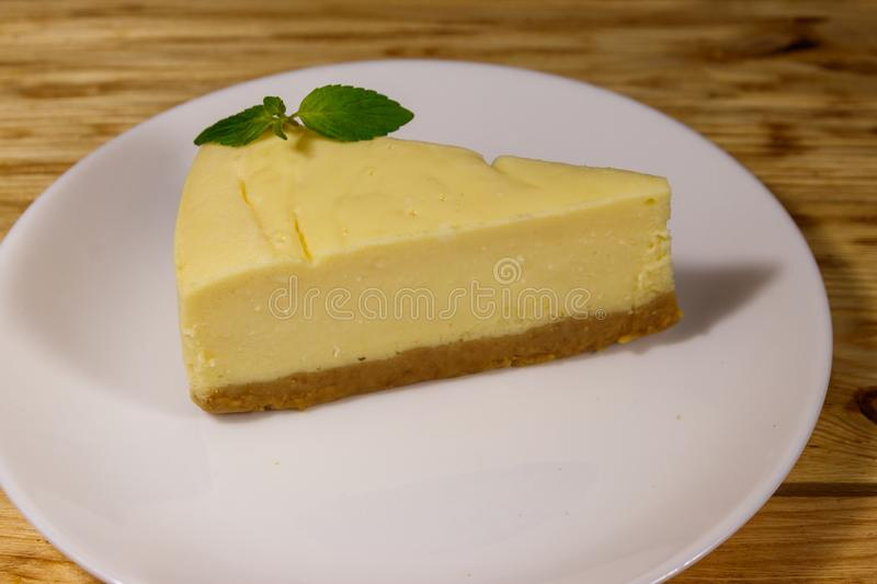 Piece of tasty sweet New York cheesecake in a white plate on wooden table. Piece of tasty sweet New York cheesecake in a white plate on a wooden table royalty free stock photos