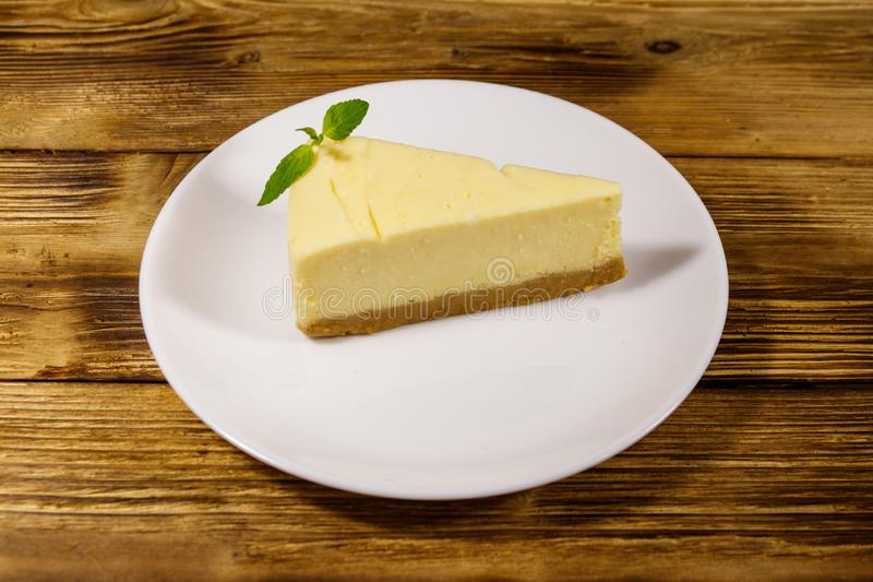 Piece of tasty sweet New York cheesecake in a white plate on wooden table. Piece of tasty sweet New York cheesecake in a white plate on a wooden table stock images