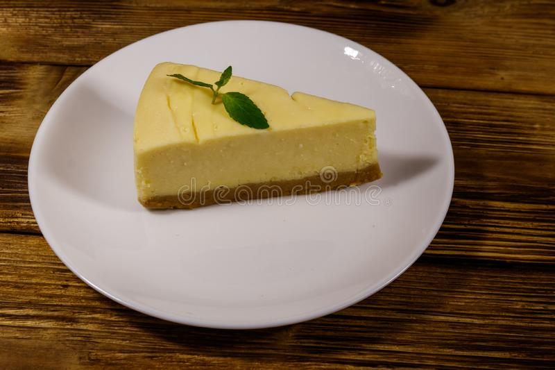 Piece of tasty sweet New York cheesecake in a white plate on wooden table. Piece of tasty sweet New York cheesecake in a white plate on a wooden table royalty free stock images